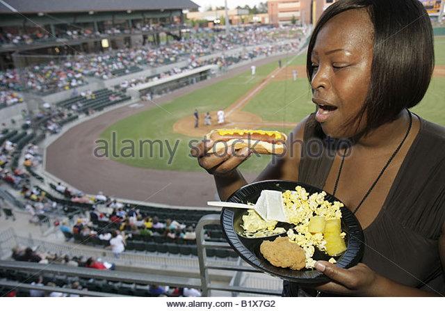 Arkansas North Little Rock Dickey Stephens Park minor league baseball Arkansas Travelers Black woman eat hot dog - Stock Image