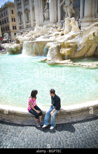 Young couple sitting at Trevi Fountain - Stock Image