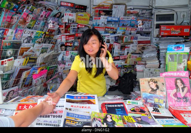 China Beijing Guang An Men Nei Da Jie Guanganmen Outer Street newsstand magazines sale Asian woman job - Stock Image