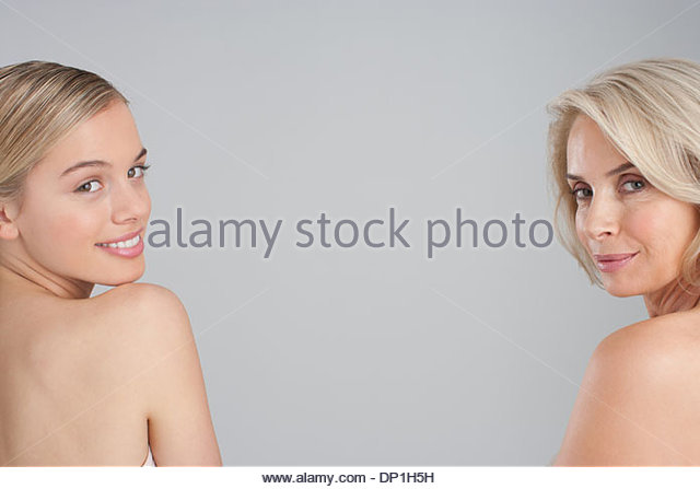 Rear view of bare chested mother and daughter laughing - Stock Image