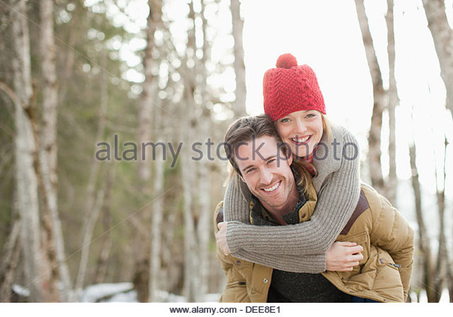 Portrait of smiling couple piggybacking in woods - Stock Image