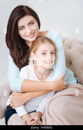 Attractive caring mother hugging her daughter - Stock Image