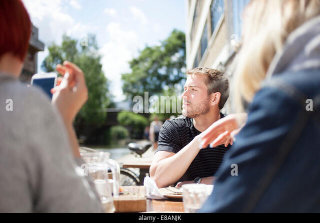 Friends having lunch by canal - Stock Image