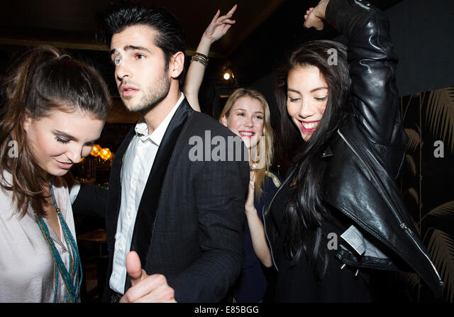 Young adults dancing at night club - Stock Image