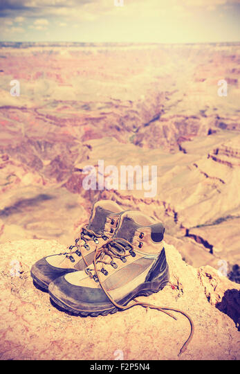Vintage toned old trekking shoes standing on south rim of Grand Canyon, adventure concept photo. - Stock-Bilder
