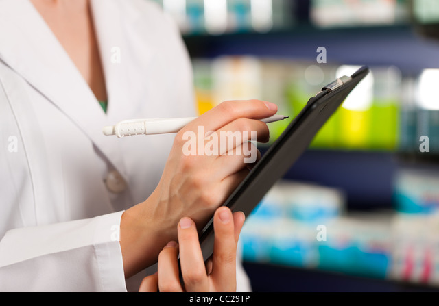 Female pharmacist or assistant is doing inventory or order taking in pharmacy - Stock Image