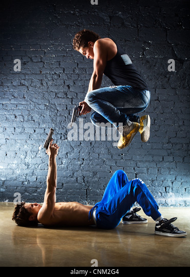 Men with guns fighting. Contrast colors. - Stock Image