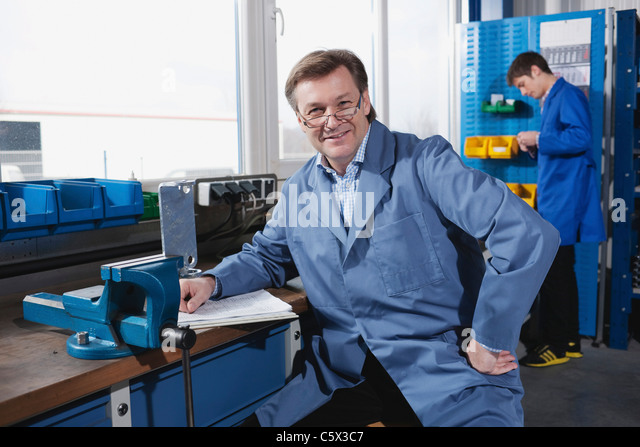 Germany, Neukirch, Man sitting at work bench, Apprentice in background - Stock-Bilder