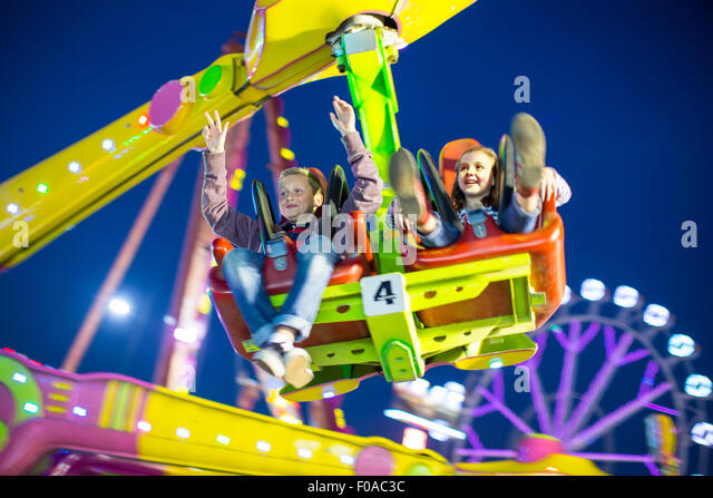 Sister and brother mid air on fairground ride at night - Stock Image