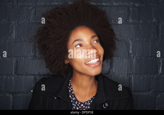 Young woman by black brick wall looking away - Stock-Bilder