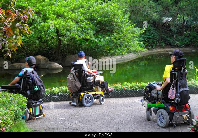 Hong Kong China Island Central Hong Kong Park landscape trees pond Asian man electric wheelchair disabled handicapped - Stock Image