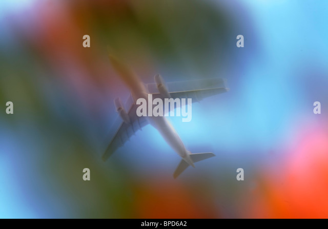 Seen through garden trees, a jet airliner passes overhead in bright skies, blurred purposely using a slow camera - Stock Image
