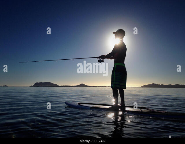 Another day at Kaneohe Bay. Fishing at sunrise. Stand up paddle wake up. - Stock Image