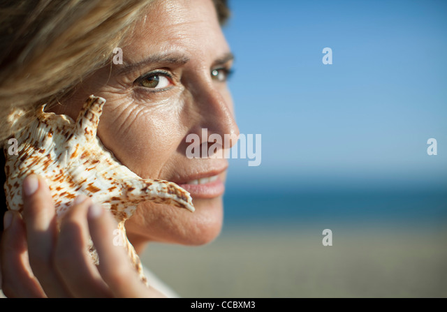 Woman listening to seashell - Stock Image