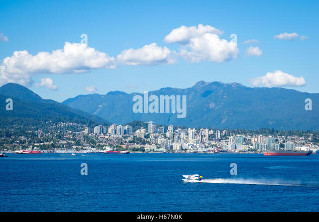 A floatplane gets ready to take off in Vancouver Harbour.  North Vancouver, British Columbia, Canada is in the distance. - Stock Image