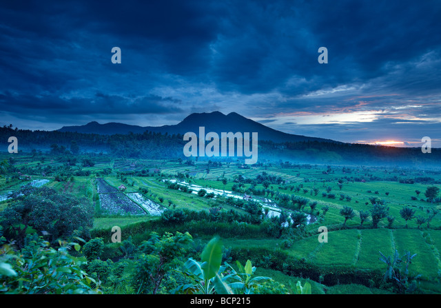 terraced rice fields near Tirtagangga at dawn with the sun rising over the volcanic peak of Gunung Lempuyang, Bali, - Stock Image