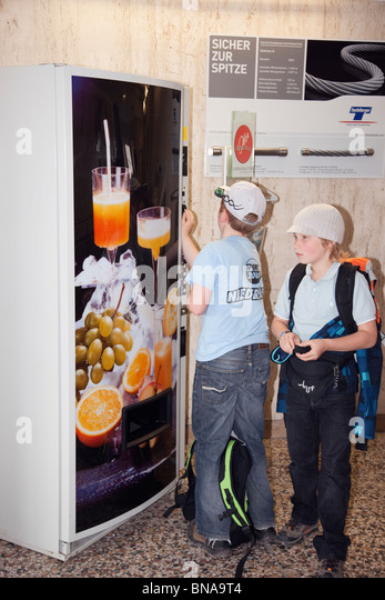 Child paying money into a drinks vending machine to buy a cold soft drink. - Stock Image