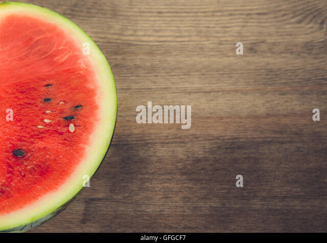 Cropped image of a sliced watermelon shot on a wooden studio surface. - Stock Image