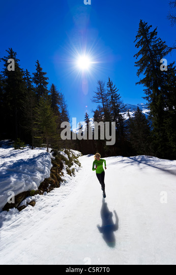 A girl jogging at high altitude in snowy mountains. - Stock-Bilder