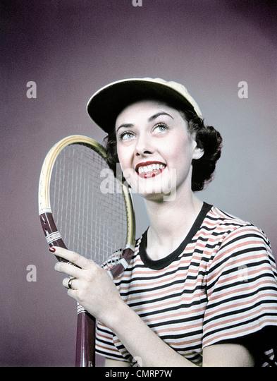 1950s SMILING BRUNETTE WOMAN HOLDING TENNIS RACKET WEAR STRIPED SHIRT CAP - Stock Image