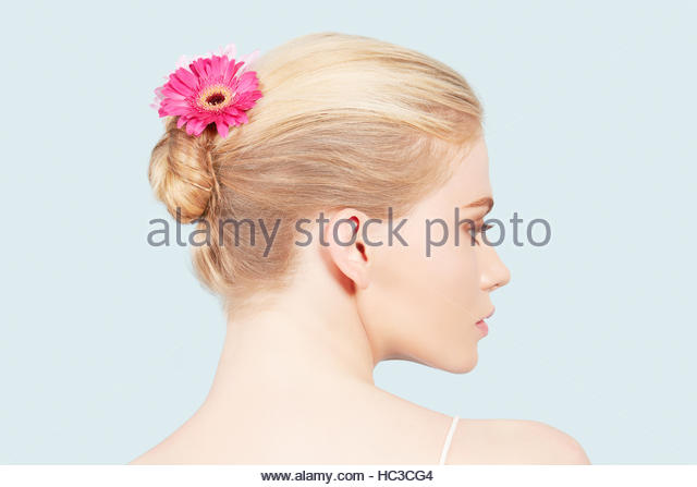 Young woman with flower in her hair. - Stock Image