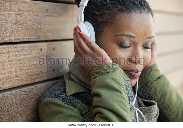 Relaxed woman listening to music outdoors - Stock-Bilder