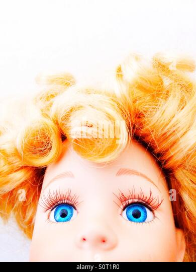 A close up of a doll's huge blue eyes. - Stock Image