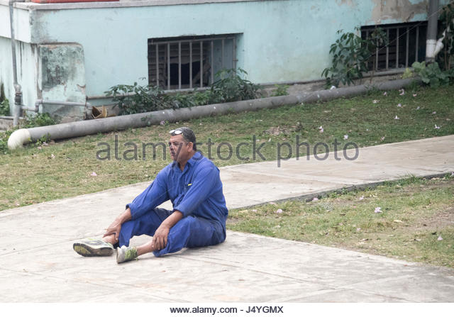 Man in overall sitting in the sidewalk. Real Cuban people lifestyle at the entrance of Havana city, the Cuban capital. - Stock-Bilder