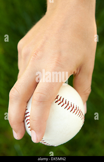 Man's hand holding baseball in pitching stance, close up, high angle view - Stock Image