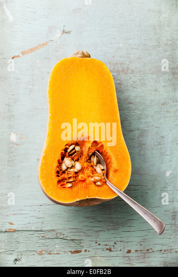 Half cut of ripe butternut squash on blue background - Stock Image