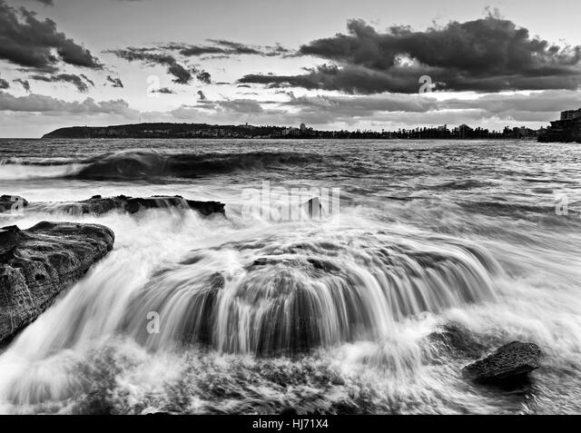 Dramatic strong wave overflows over sandstone boulder at Freshwater beach north of Manly in Sydney, Australia. Black - Stock Image
