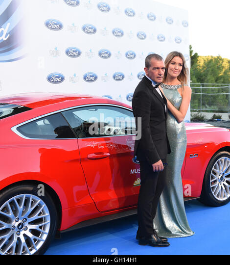 Actor Antonio Banderas and his partner infront of a red Ford Mustang Car which had been Autographed by Antonio Banderas - Stock Image