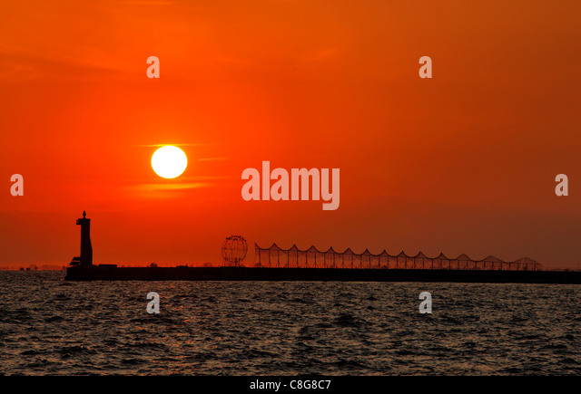 An artistic installation and the lighthouse at the breakwater of Thessaloniki port, at sunset. Macedonia, Greece. - Stock Image