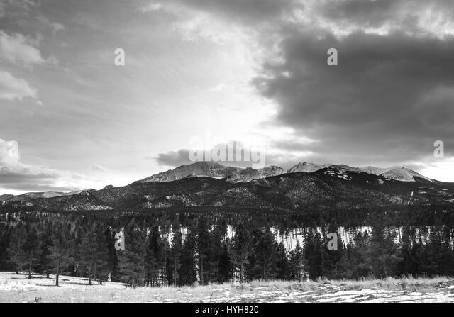 Snow capped mountain range on private property with a no trespassing sign. The driveway leads to an open field with - Stock Image