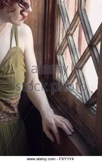 Woman in vintage 1940s dress by window - Stock-Bilder