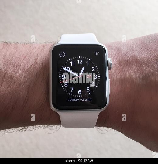 The Apple Watch white, sport, smartwatch shown top down on the wrist being activated to show the time in utility - Stock Image