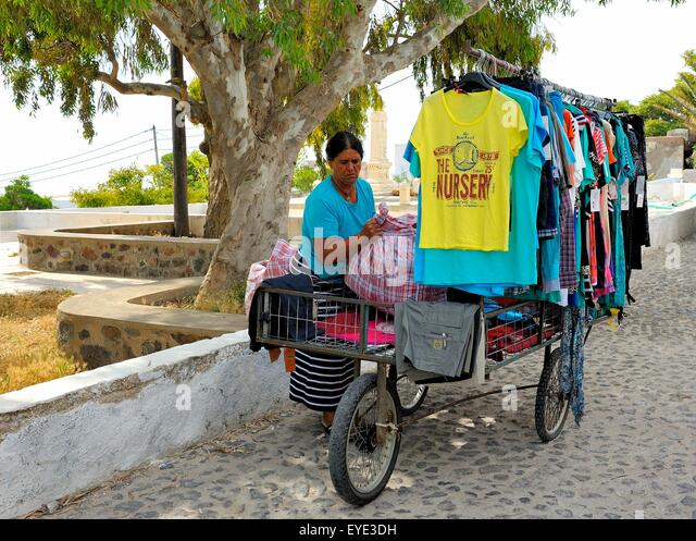 A local woman with a mobile market stall selling children's clothing. Santorini,Greece - Stock Image