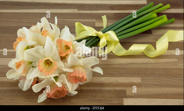 Bunch of daffodils tied with ribbon placed on an oak worktop. - Stock Image