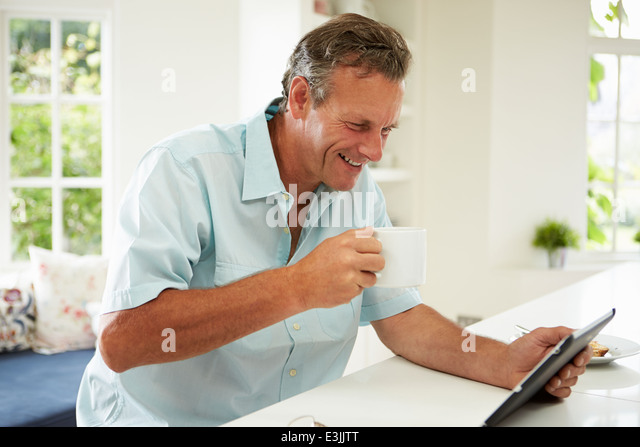 Middle Aged Man Using Digital Tablet Over Breakfast - Stock Image