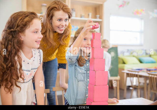Students and teacher stacking blocks in classroom - Stock Image