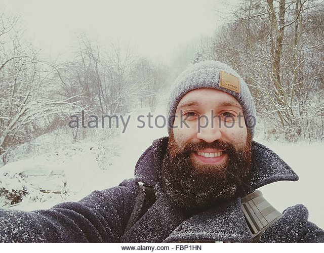 Portrait Of A Cheerful Young Man In Snow - Stock-Bilder