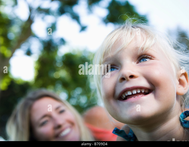 Portrait of a mom and a four year old girl in a park. - Stock Image