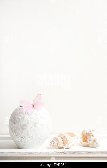 minimalist white vase with pink butterfly and shells against white wall - Stock Image
