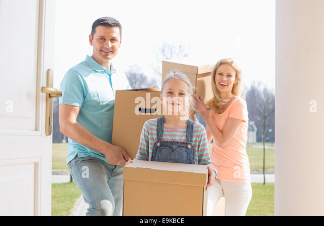 Happy family with cardboard boxes entering new home - Stock Image