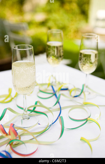 Champagne flutes on table decorated with party streamers - Stock Image