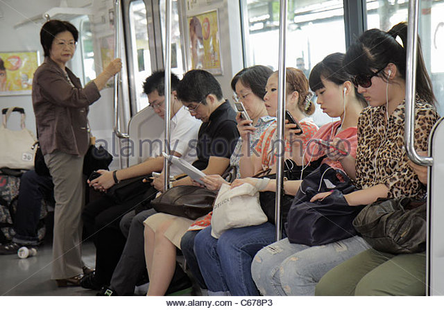 Tokyo Japan Ikebukuro Ikebukuro Station JR Yamanote Line train subway passengers Asian man woman standing sitting - Stock Image