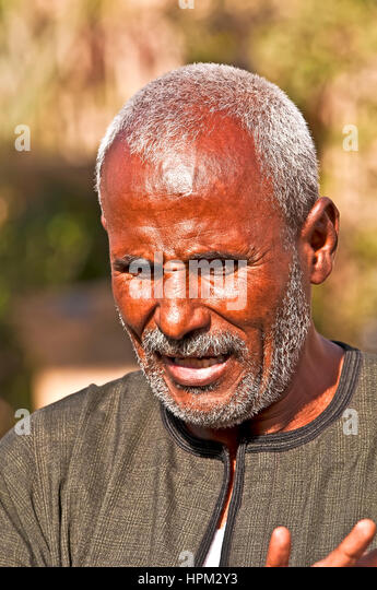 Egyptian boatman on ferry taking tourists to temple at Philae Island - Stock Image