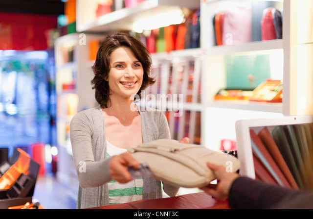 Woman buying purse in store - Stock Image