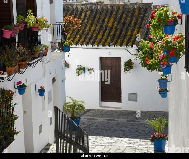 Estepona Old town quaint streets flower pots geraniums terra-cotta rooftops cobbled streets white village pueblo - Stock Image