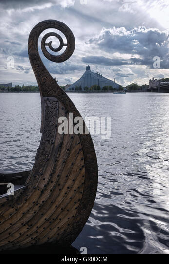 Nose Viking boat on the River Daugava on the background of the Latvian National Library with beautiful olakami in - Stock Image